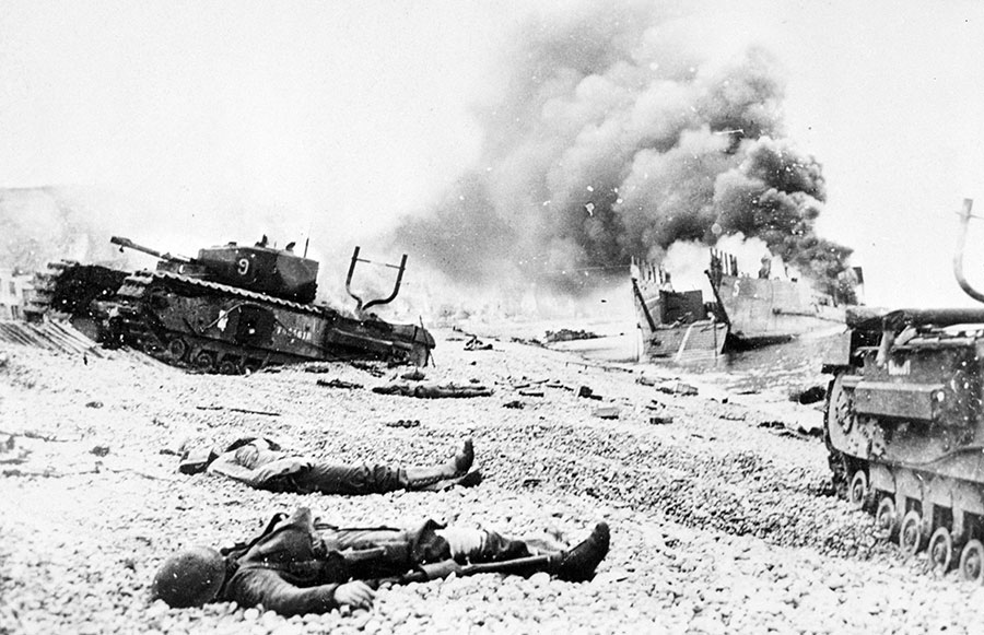 Canadian casualties lie among damaged landing craft and Churchill tanks